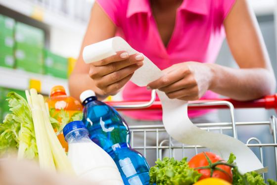 Woman holding a grocery bill shutterstock Stokkete
